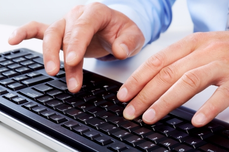 Hands of businessman with a computer keyboard. Imagens