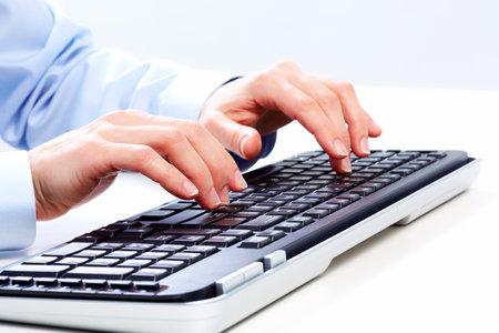 コンピューターのキーボードと実業家の手。
