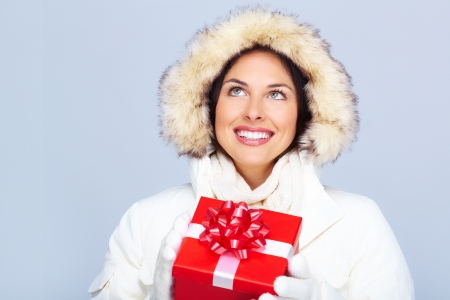 Beautiful christmas girl with gift. Over winter background. Stock Photo