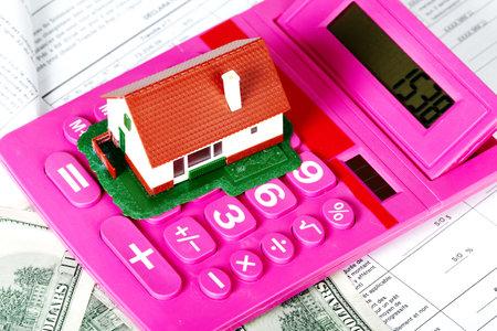 家と電卓。不動産の概念の背景。 写真素材