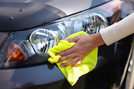 Hand met microfiber doekje schoonmaken auto. Stockfoto