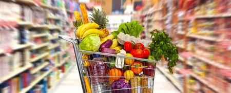 スーパー マーケットでフルのショッピング食料品のカート。