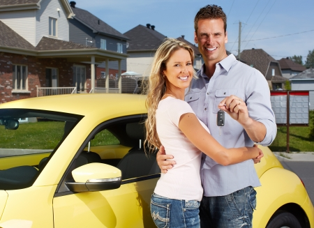 Happy young couple near new car with a key  Imagens