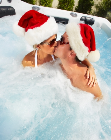 Happy christmas santa couple in hot tub  Vacation
