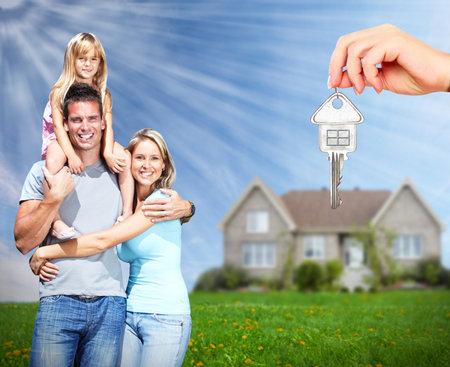 Gelukkige familie in de buurt van het nieuwe huis. Onroerend goed achtergrond. Stockfoto