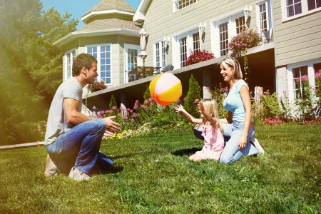 Happy smiling family with child over  house background Stock Photo - 22218682