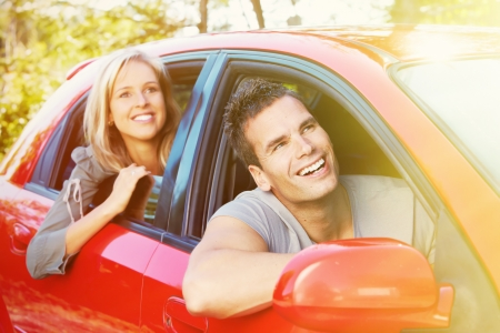 Two young smiling people in a red car