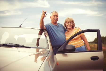 Two happy smiling elderly people in car with keys Stockfoto