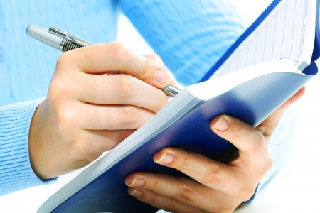 Hands of business woman writing in agenda. Stock Photo - 22219135
