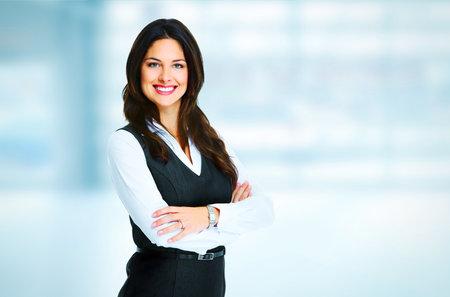 オフィスの背景の上に立っている若い商務女性