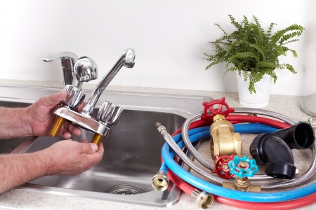 Hands of professional Plumber with a water tap  Banco de Imagens