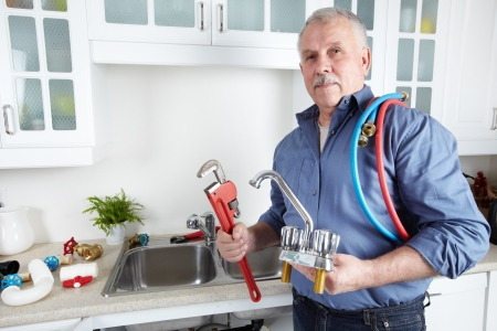 Plumber in kitchen with a wrench. Foreman.