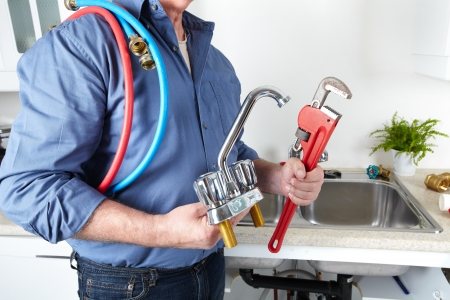 Hands of professional Plumber with a water tap and wrench. Banque d'images