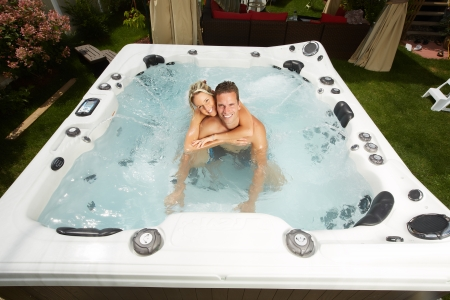 Happy couple relaxing in hot tub. Vacation. Фото со стока