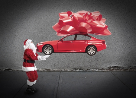 Santa claus with car gift. Christmas holiday background.