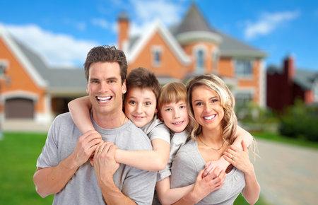 Gelukkige familie dichtbij nieuwe huis Onroerend goed achtergrond Stockfoto