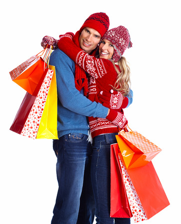 Happy couple with christmas shopping bags isolated over white background Stock Photo
