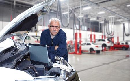 Meccanico auto maturo che lavora nel servizio di riparazione auto