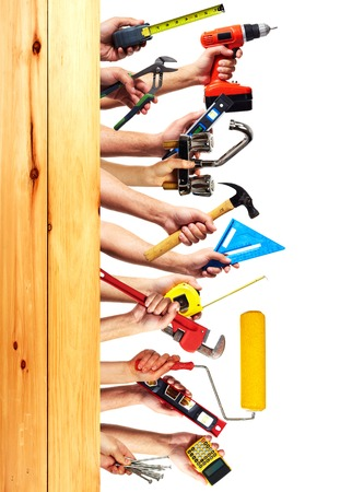 Hands with construction tools. House renovation background.