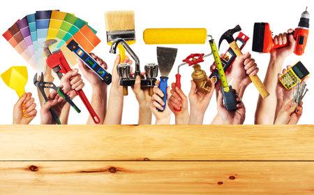 Mani con strumenti di costruzione. Casa da ristrutturare sfondo. Archivio Fotografico