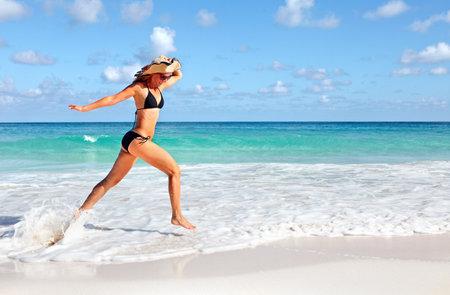 Happy woman running on the beach. Reklamní fotografie