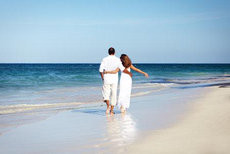 Loving couple walking on sandy beach. Stock Photo