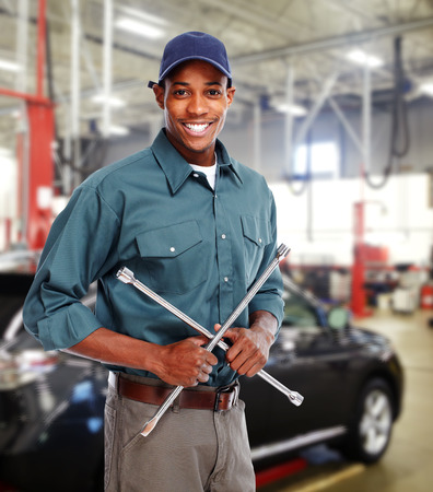 Werktuigkundige met moersleutel in de garage.