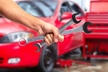 Hand of car mechanic with wrench.