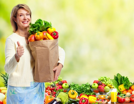 Woman with Vegetables over green background. Stock Photo