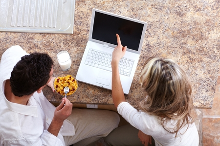 Young couple with laptop computer at home.