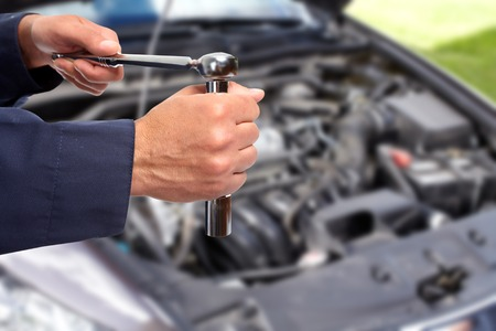 Hand of car mechanic with wrench. Auto repair garage. Banco de Imagens