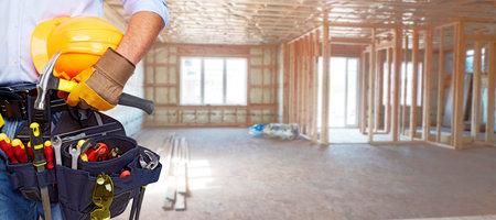 Costruttore tuttofare con strumenti di costruzione. Ristrutturazione casa sfondo. Archivio Fotografico - 44873542