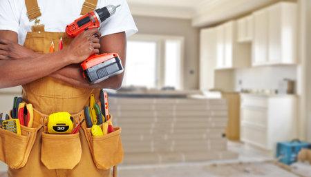 Złota rączka budowniczy z narzędzi budowlanych. Remont domu w tle. Zdjęcie Seryjne