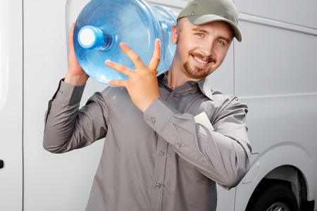 Water delivery service man with big bottle. Stock Photo