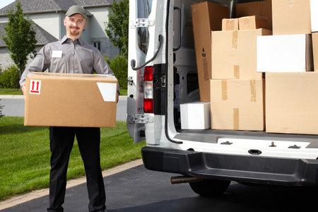 Hombre de salida joven con parcela cerca de camión de carga. Servicio de envío.
