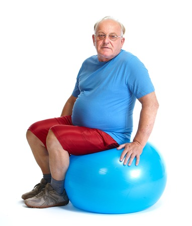 Elderly man sitting on exercise ball. Sport and health.