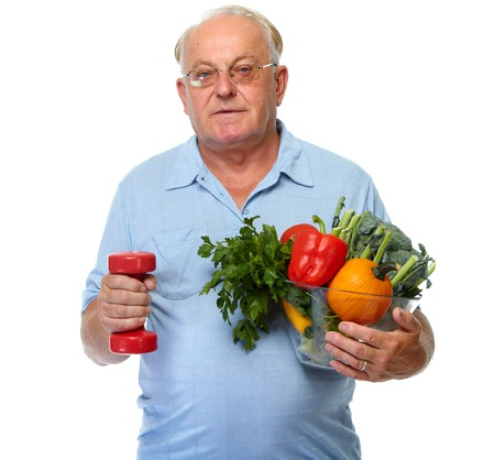 Elderly man with vegetables and dumbbell isolated over white background. Stock Photo