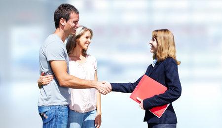 Jeune couple avec l'agent agent immobilier sur fond bleu. Banque d'images - 45541546