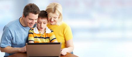 Familia con el ordenador portátil sobre fondo azul bandera.
