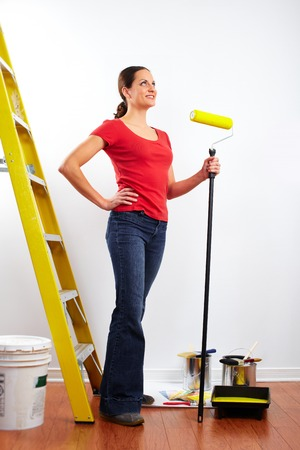 Beautiful woman with painting roller. House renovation. Banco de Imagens