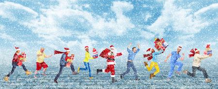 Gelukkige lopende Kerstmis mensen boven de besneeuwde achtergrond Stockfoto