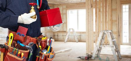 Bouwer klusjesman met de bouw gereedschap. Huis renovatie achtergrond.