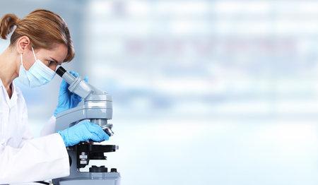 Doctor woman with microscope in laboratory. Scientific research. Archivio Fotografico
