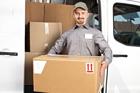 화물 트럭 근처 소포 젊은 배달 남자. 배송 서비스를 제공합니다.