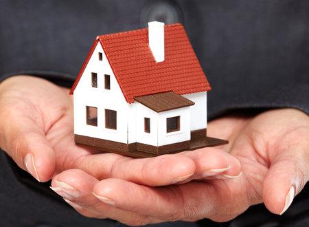 Mani con casetta. Immobiliare e la costruzione di sfondo.