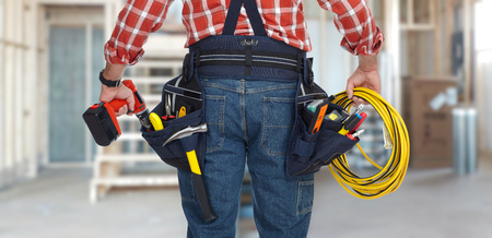 Electrician man with drill and wire cable over construction background. Stock Photo