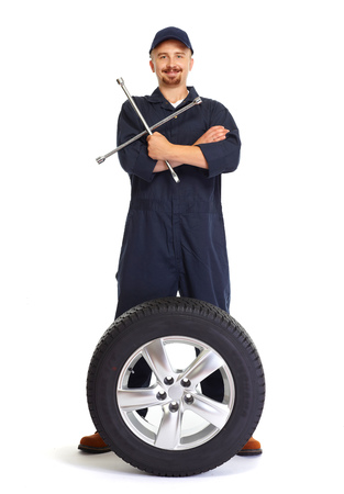 Smiling car mechanic with a tire isolated on white background.