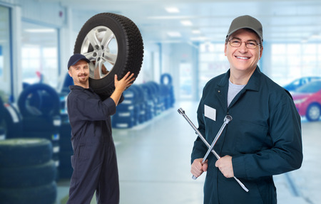 Smiling repairman with tire wrench in car repair service. 스톡 콘텐츠