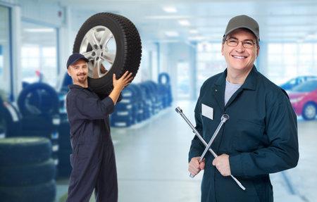 Glimlachen reparateur met de band moersleutel in de auto reparatie service.