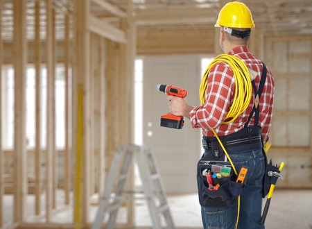 Electrician man with drill and wire cable over construction background. Archivio Fotografico